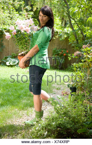 Woman in garden carrying potted lilies - Stock Photo