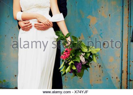 groom hugs his bride, medium close-up - Stock Photo