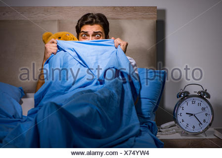 Young man scared in bed - Stock Photo
