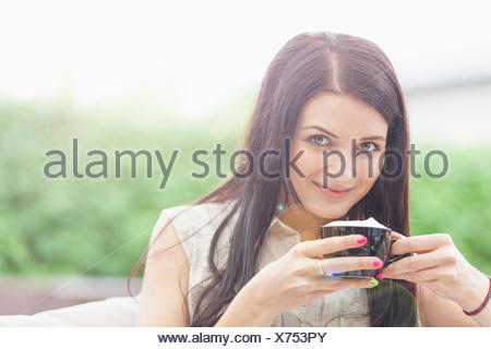 Young woman taking coffee break - Stock Photo