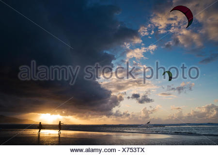 Two kite surfers on beach, Los Lances beach, Tarifa, Andalucia, Spain - Stock Photo