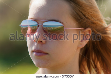 Portrait Of A Young Woman Wearing Sunglasses With The Landscape Reflected In Them; Tarifa Cadiz Andalusia Spain - Stock Photo
