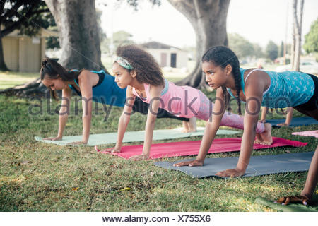 Girls and teenage schoolgirls practicing yoga plank pose on school playing field - Stock Photo