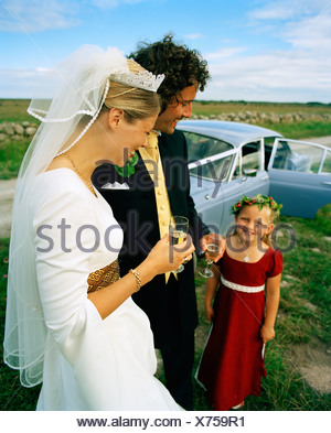 Scandinavia, Sweden, Oland, Bride and groom with flower girl, smiling - Stock Photo