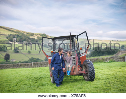 Farmer and young son sitting on tractor in field - Stock Photo