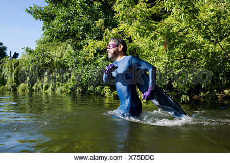 Side view of mature superhero running in river against trees - Stock Photo
