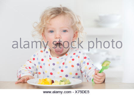 Baby eating fruit making a face - Stock Photo