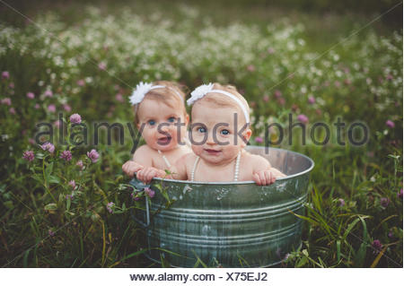 Portrait of baby twin sisters bathing in a tin bathtub in a wild flower meadow - Stock Photo