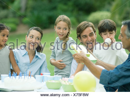 Outdoor birthday party, mature man handing girl presents - Stock Photo