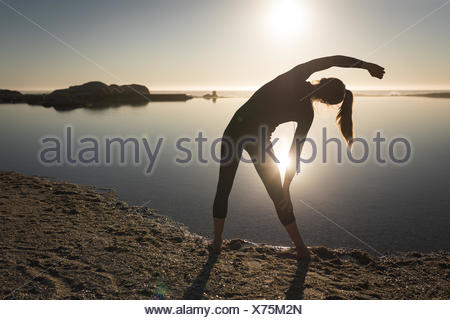 Woman performing stretching exercise near coast - Stock Photo