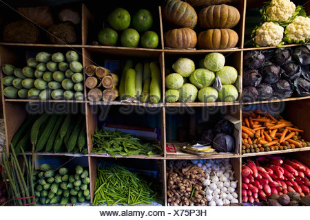 India, Ooty, Variety of vegetables in cupboard at market - Stock Photo
