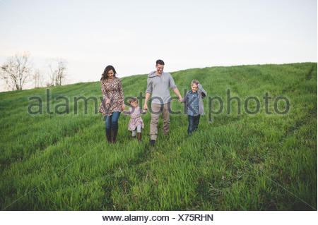 Parents with son and daughter strolling in grassy field - Stock Photo