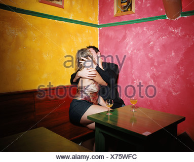 Couple kissing in corner of bar - Stock Photo