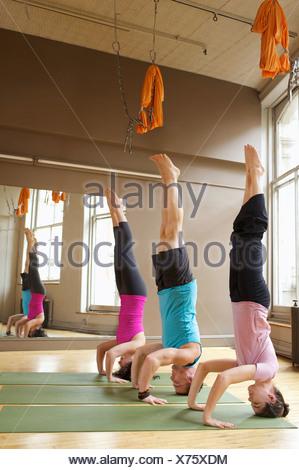 People doing headstands (Salamba-Shirshasana) in yoga class - Stock Photo