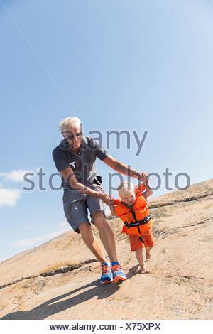 Sweden, Sodermanland, Vastra Stendorren, Man with boy (12-17 months) walking on rocks - Stock Photo