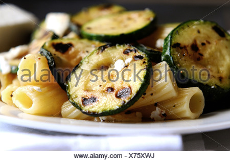 Pasta with fried courgette slices - Stock Photo