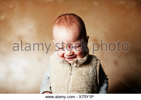 Portrait of cute baby boy looking down and giggling - Stock Photo