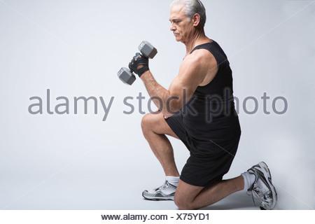 Senior man in sports clothing lifting broccoli - Stock Photo