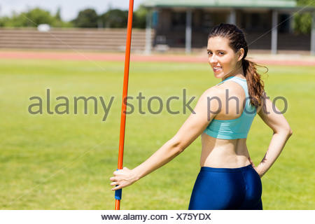 Portrait of female athlete standing with javelin - Stock Photo