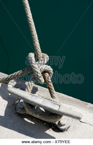 A rope tied to jetty cleat - Stock Photo