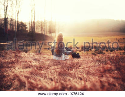 Rear view of woman sitting outdoors - Stock Photo