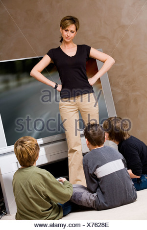 Woman frustrated with boys for playing video game - Stock Photo
