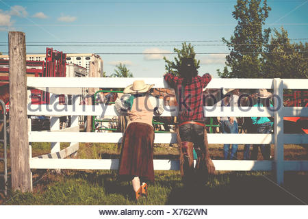 USA, Connecticut, Rear view of couple at rodeo leaning on cattle fence - Stock Photo
