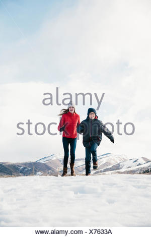 Two children, brother and sister running across the snow. - Stock Photo
