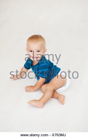 baby sitting on floor in diapers - Stock Photo