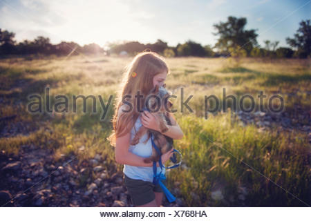 Girl carrying her dog on hike - Stock Photo