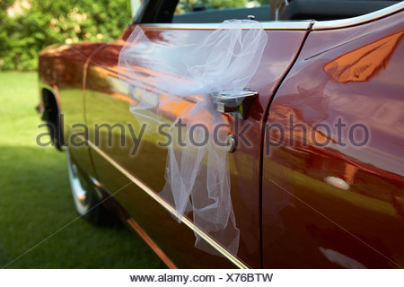 Tulle netting, veil tied to a Cadillac, wedding - Stock Photo
