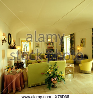 Large floral arrangement on floor behind pastel green sofa in country living room with cream flooring - Stock Photo