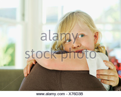 A little girl hugging a loved one - Stock Photo