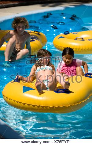 Children having fun at water park floating on innertubes - Stock Photo