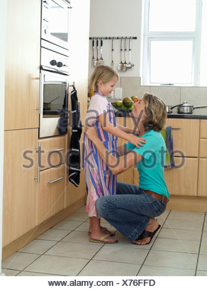 Mother and daughter 6 8 standing in kitchen girl wearing striped apron woman tying knot smiling - Stock Photo