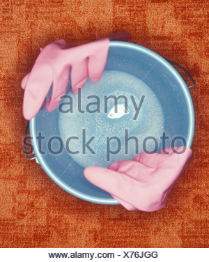 High angle view of gardening gloves at edge of bucket - Stock Photo