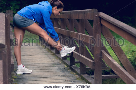 Healthy woman stretching her leg during exercise on footbridge - Stock Photo