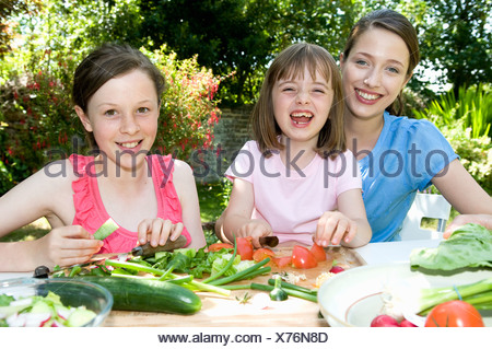 Happy mother and daughters prepare food - Stock Photo