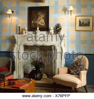 Paint effect yellow and blue check walls in living room with ornate marble fireplace and small cream armchair - Stock Photo