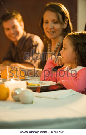 Girl sitting at dinner table with family, looking away - Stock Photo