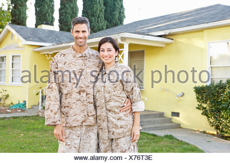 Military Couple In Uniform Standing Outside House - Stock Photo