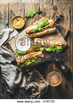 Glasses of wheat unfiltered beer and grilled sausage dogs in baguette with mustard, caramelised onion and herbs on serving board - Stock Photo