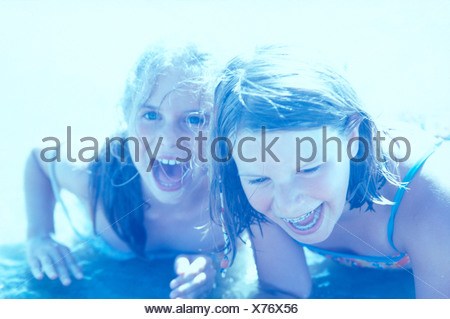 Close-up of two teenage girls playing in water on beach - Stock Photo