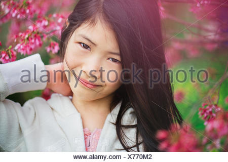Portrait young girl (8-9) in flowers - Stock Photo