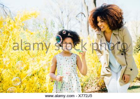 Front view of mother and daughter blowing bubbles
