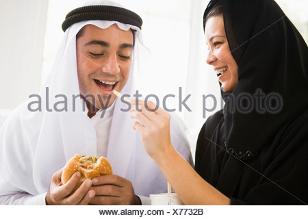 Couple eating fast food in living room and smiling (high key/selective focus) - Stock Photo