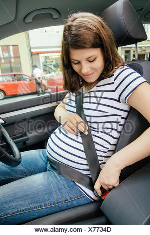 Pregnant woman fastening safety belt in her car - Stock Photo