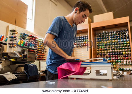 Worker using embroidery machine in t-shirt printing workshop - Stock Photo