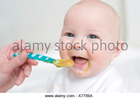 Spoon-feeding. 7 month old baby girl being spoon-fed. - Stock Photo