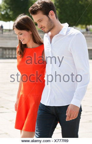 Couple walking with arms around and smiling, Paris, Ile-de-France, France - Stock Photo